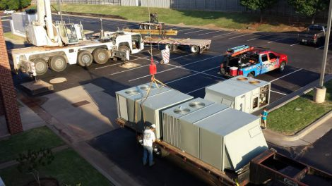 Prudhom pros providing commercial HVAC services outside a commercial building in Edmond, OK.