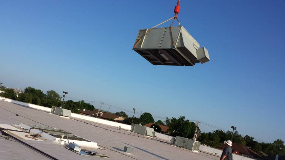 Prudhom HVAC contractors lifting commercial ac unit for an ac install in Edmond, OK